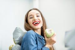 Retrato de uma mulher com sorriso saudável no escritório dental fotografia de stock royalty free