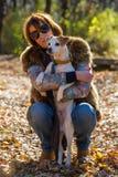 Retrato de uma mulher com um cão no feriado no parque do outono,  Fotos de Stock