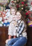 Retrato de uma mulher com uma criança perto da árvore de Natal Foto de Stock Royalty Free