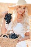 Retrato de uma mulher com a uva nas mãos Imagens de Stock