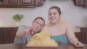 Retrato de uma mulher consideravelmente gorda e de um homem louro magro na cozinha na tabela na frente de uma placa grande com ma vídeos de arquivo