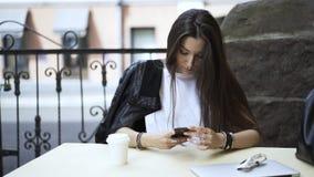 Retrato de uma mulher de cabelo preta nova em um café com um smartphone video estoque