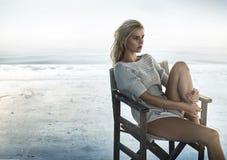 Retrato de uma mulher de fascínio que senta-se na cadeira retro Foto de Stock