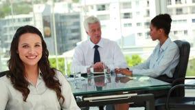 Retrato de uma mulher de negócios bonita com os colegas no fundo Fotografia de Stock Royalty Free