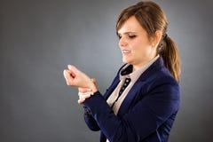 Retrato de uma mulher de negócios nova que sofre da dor do pulso Imagem de Stock Royalty Free
