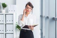 Retrato de uma mulher de negócios que tem a chamada do negócio, discutindo detalhes, planeando suas reuniões usando o diário e o  Fotos de Stock Royalty Free