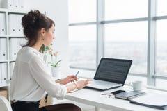 Retrato de uma mulher de negócios que senta-se em seu local de trabalho no escritório, datilografia da vista traseira, olhando a  Fotos de Stock