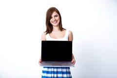 Retrato de uma mulher de sorriso que mostra a tela do portátil Fotografia de Stock