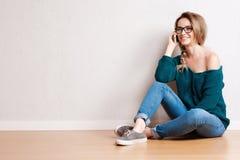 Retrato de uma mulher de sorriso que senta-se no assoalho e que fala no telefone no fundo cinzento Fotos de Stock