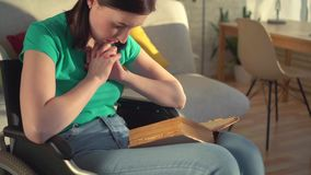Retrato de uma mulher deficiente nova em uma cadeira de rodas que lê uma oração