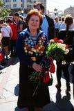 Retrato de uma mulher do veterano de guerra que sorri guardando flores em botão Foto de Stock