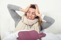 Retrato de uma mulher doente que senta-se na cama imagens de stock royalty free
