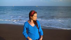 Retrato de uma mulher em um vestido azul bonito em uma praia vulcânica preta Filmado nas velocidades diferentes - aceleradas e video estoque