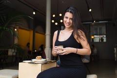 Retrato de uma mulher encantador que aprecia o café ao descansar após o trabalho em seu tablet pc digital, imagens de stock
