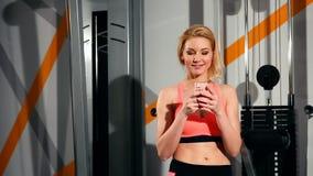 Retrato de uma mulher feliz da aptidão que usa o smartphone no gym filme