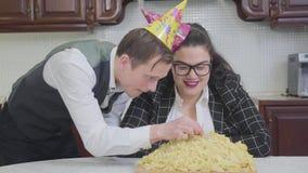 Retrato de uma mulher gorda bonito na tabela na frente de uma placa grande com os macarronetes em vez do bolo na cozinha slim vídeos de arquivo