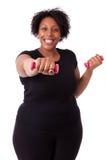 Retrato de uma mulher gorda preta que da certo com pesos livres - Imagem de Stock Royalty Free