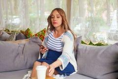 Retrato de uma mulher gravida nova lindo que aprecia uma xícara de café ou um chá no café, mulher de negócio, gravidez ativa foto de stock