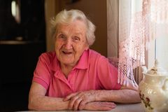 Retrato de uma mulher idosa do pensionista que senta-se em uma tabela na cozinha em sua casa imagem de stock