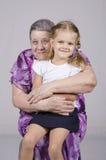 Retrato de uma mulher idosa que cobre sua neta Fotos de Stock