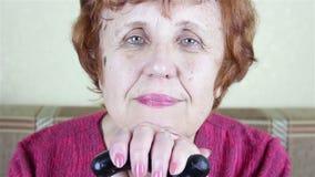 Retrato de uma mulher idosa Sits que inclina-se em uma vara de passeio video estoque