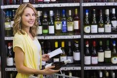 Retrato de uma mulher loura bonita de sorriso que tem em suas mãos uma garrafa e um bloco de notas de vinho Imagens de Stock Royalty Free