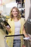 Retrato de uma mulher loura bonita de sorriso que tem uma garrafa do bloco de notas e de vinho em suas mãos Foto de Stock