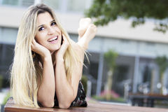 Retrato de uma mulher loura bonita que encontra-se em um banco Imagem de Stock