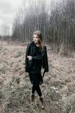 Retrato de uma mulher loura nova em um revestimento preto nas madeiras fotos de stock