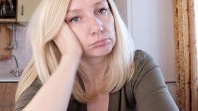 Retrato de uma mulher loura nova triste e furada que senta-se no conceito da cozinha, da tristeza e da depressão video estoque