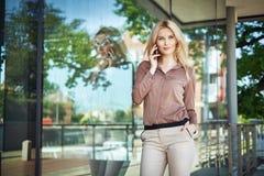 Retrato de uma mulher loura que guarda um smartphone Foto de Stock