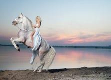 Retrato de uma mulher loura que monta um cavalo Fotografia de Stock Royalty Free