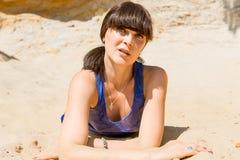 Retrato de uma mulher moreno nova que encontra-se em uma areia Fotografia de Stock Royalty Free