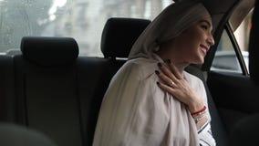 Retrato de uma mulher muçulmana nova no lenço bege, sentando-se no carro ao olhar para fora com a janela e do sorriso video estoque