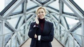 Retrato de uma mulher de negócio bonita nova, sem vidros, andando em torno da cidade na área do centro de negócios video estoque