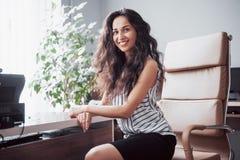 Retrato de uma mulher de negócio feliz que senta-se em seu local de trabalho fotos de stock