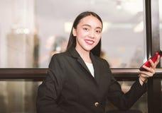 Retrato de uma mulher de negócio que usa um telefone celular que olha a câmera Foto de Stock Royalty Free