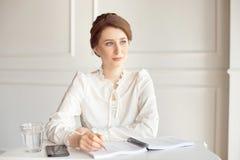Retrato de uma mulher de negócios moreno nova de sorriso bonita em uma camisa branca que senta-se em uma estação de trabalho mode fotografia de stock