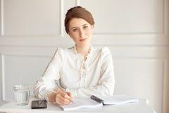 Retrato de uma mulher de negócios moreno nova de sorriso bonita em uma camisa branca que senta-se em uma estação de trabalho mode foto de stock