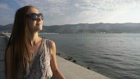 Retrato de uma mulher nova, atrativa que anda na frente marítima da cidade, tiro do steadicam filme