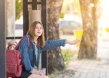 Retrato de uma mulher nova bonita de Ásia que espera um ônibus ou uma chamada algo foto de stock royalty free