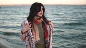 Retrato de uma mulher nova bonita na praia menina no revestimento do outono fora vídeos de arquivo