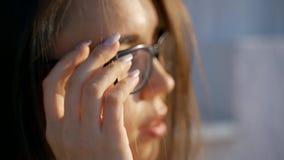 Retrato de uma mulher nova com vidros Uma menina com um sorriso atrativo põe sobre seus vidros Movimento lento Close-up filme