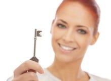 Retrato de uma mulher nova do redhead que prende uma chave Imagens de Stock Royalty Free