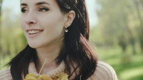 Retrato de uma mulher nova e bonita Brunette Menina em uma camiseta e nas folhas de outono em suas mãos Movimento lento vídeos de arquivo
