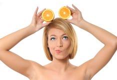 Retrato de uma mulher nova que prende laranjas frescas Fotografia de Stock