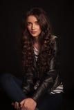 Retrato de uma mulher ocasional nova no assento do casaco de cabedal Fotos de Stock Royalty Free