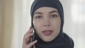 Retrato de uma mulher oriental bonita nova na roupa muçulmana moderna e na mantilha preta bonita que fala pela pilha vídeos de arquivo