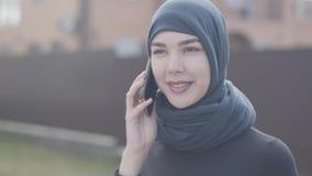 Retrato de uma mulher oriental nova na roupa preta e na mantilha bonita que fala pelo fim do telefone celular acima Mulher asiáti video estoque