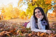 Retrato de uma mulher que aprecia as cores douradas do outono em um parque foto de stock royalty free